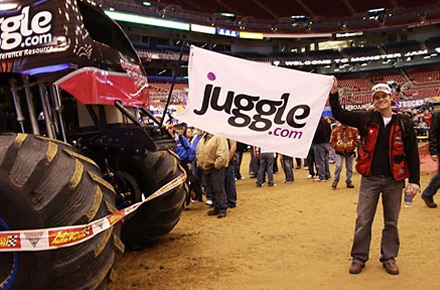 Ryan Noble holds the Juggle flag next to Bounty Hunter at Monster Jam event
