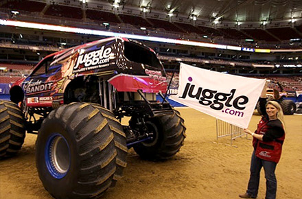 Stephani Leffler holds the Juggle flag next to monster truck Bandit at Monster Jam event