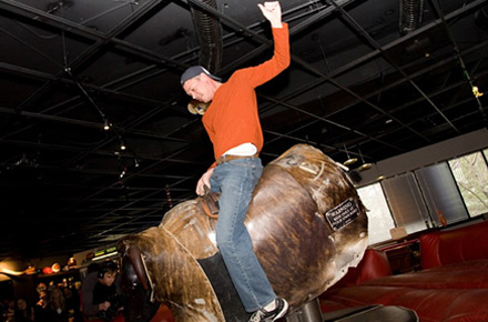 Juggle team member rides the mechical bull